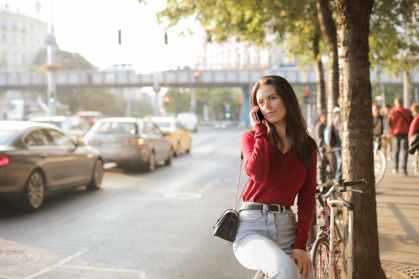 selective focus photo of woman in red long sleeve sweater and blue jeans sitting on metal railing while talking on the phone